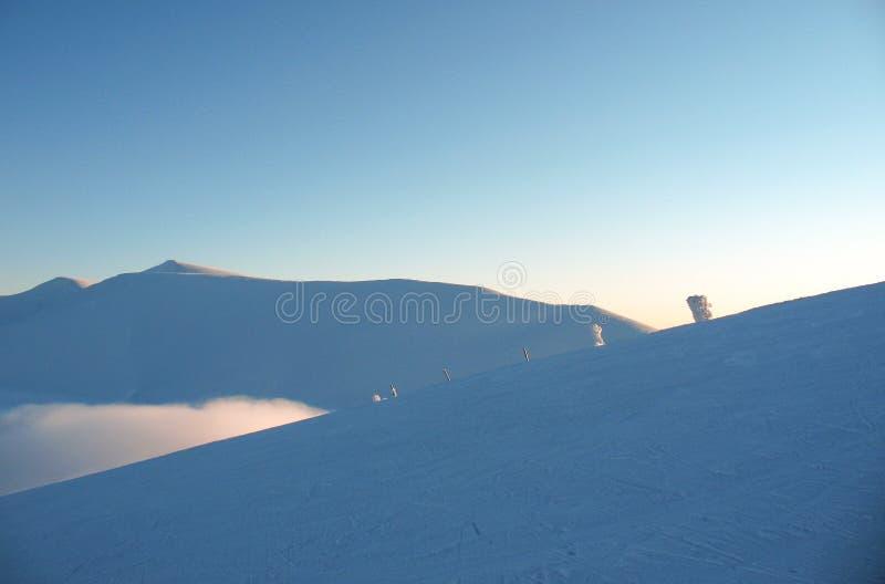 Vit snö täckte bergmaxima på höjdpunkt Öde blått extremt vinterlandskap arkivfoto