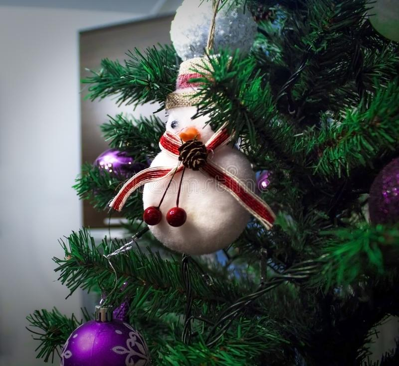 Vit snögubbe på julträdet arkivfoto