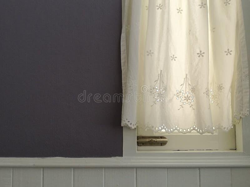 Vit snör åt satänggardinen som hänger på fönster med semitransparent solljus, tappningljus - den purpurfärgade väggen och vitsidi royaltyfri foto