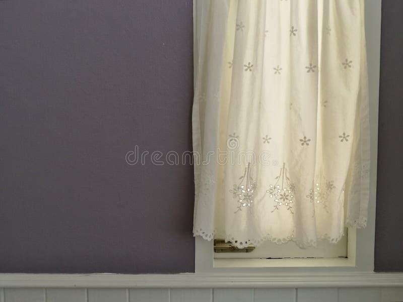 Vit snör åt satänggardinen som hänger på fönster med semitransparent solljus, tappningljus - inre rum för purpurfärgad vägggarner arkivbilder
