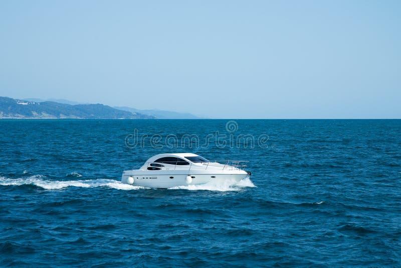 Vit snabb motorbåt i det blåa havet royaltyfri bild