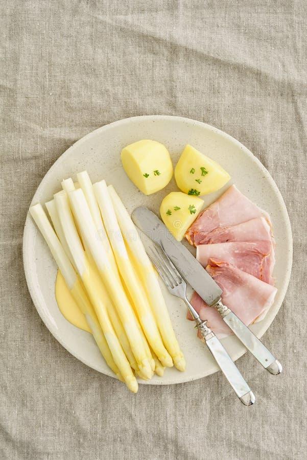 Vit sparris med potatisar och kokt skinka arkivbild