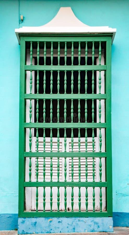 Vit stängde med fönsterluckor fönstret med gröna trästänger på den blåa väggen, newl fotografering för bildbyråer
