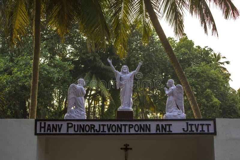 Vit staty av Jesus med två änglar på en bakgrund av gröna palmträd arkivbild