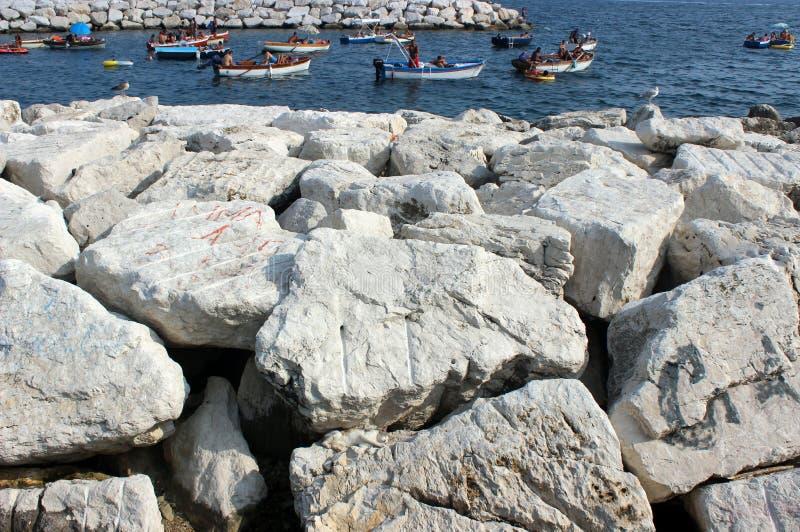 Vit stenar stranden och semesterfirare på fartyg royaltyfri fotografi