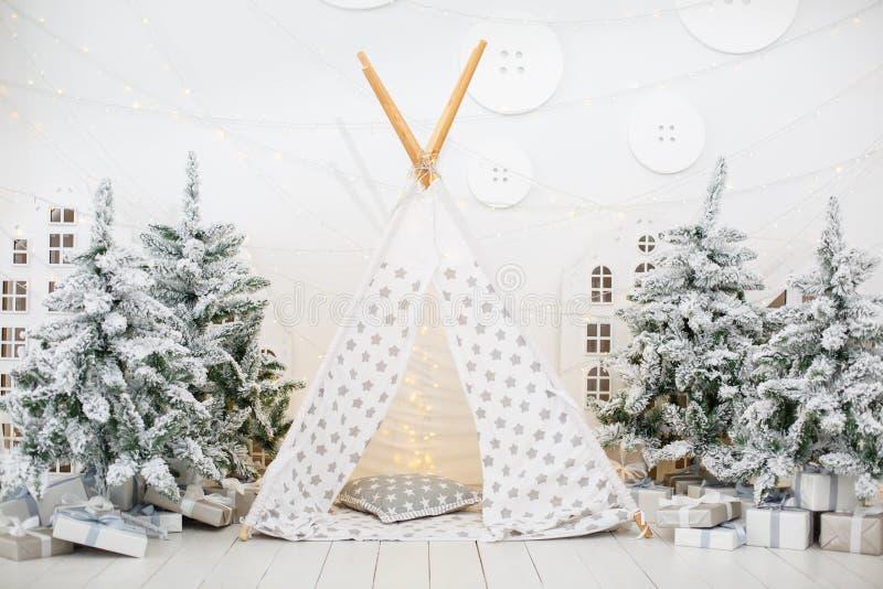 Vit stilfull inre med den lilla vigvammet för julgranträd- och barnlek arkivfoton