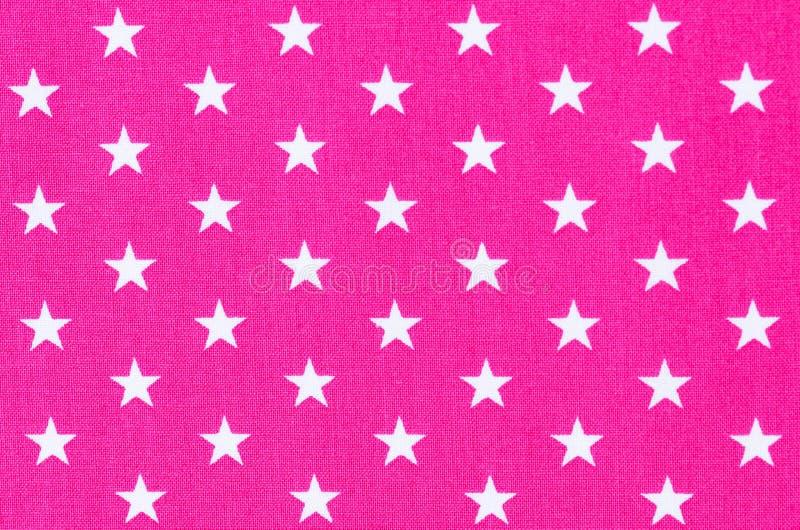 Vit stjärnamodell på rosa tygbakgrundstextur arkivfoton