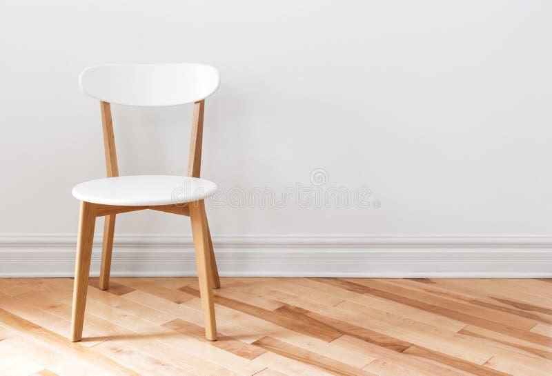 Vit stol i ett tomt rum fotografering för bildbyråer