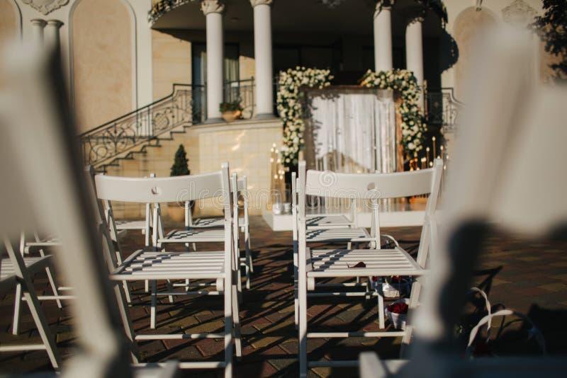 Vit stol på bröllopceremoni sommarbröllopgarnering utanför arkivfoto