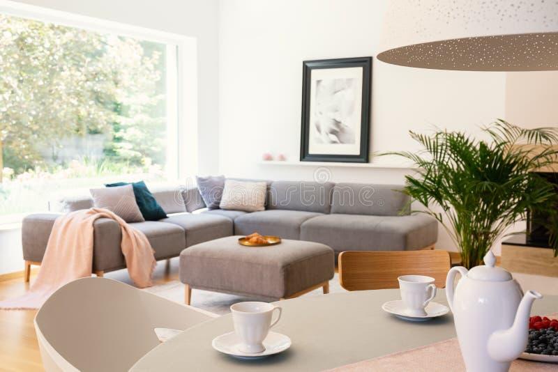 Vit stol på tabellen i ljus lägenhetinre med grå färger konserverar arkivbild