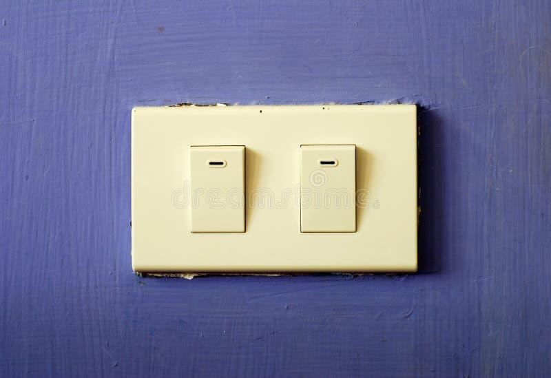 Vit strömbrytare på den blåa väggen arkivbild