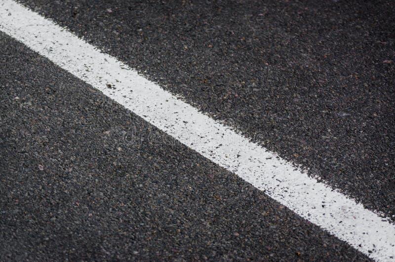 Vit strimma av målarfärg på grå asfalt royaltyfri fotografi