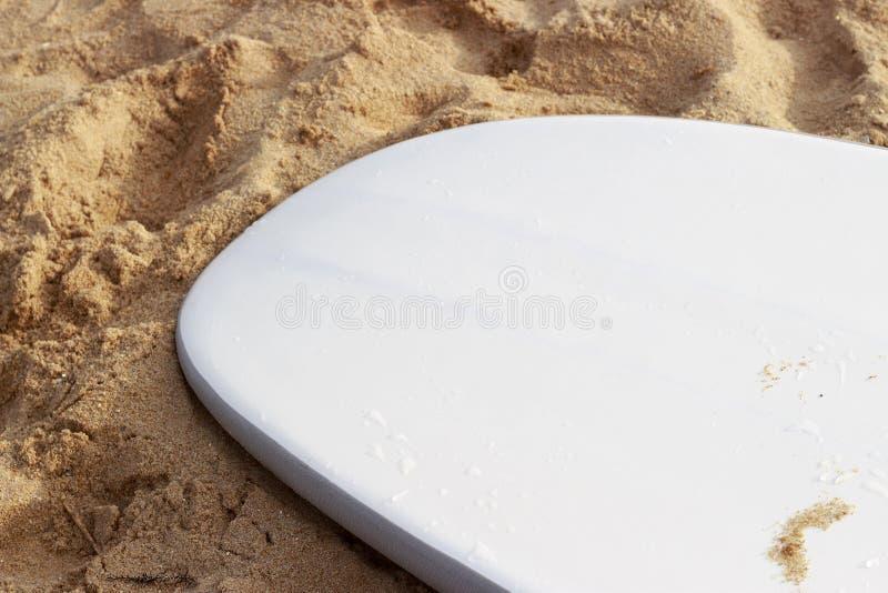 Vit surfingbräda som ligger på sikten för sandnärbildsida arkivbilder