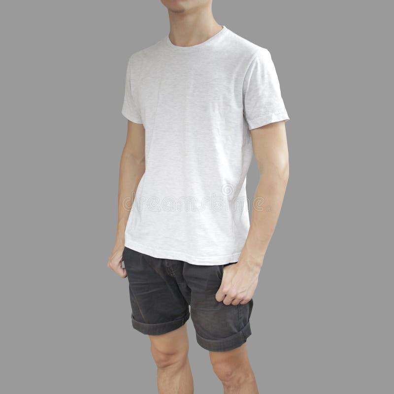 Vit t-skjorta och svartkortslutningar på en mall för ung man på grå färger b royaltyfri bild