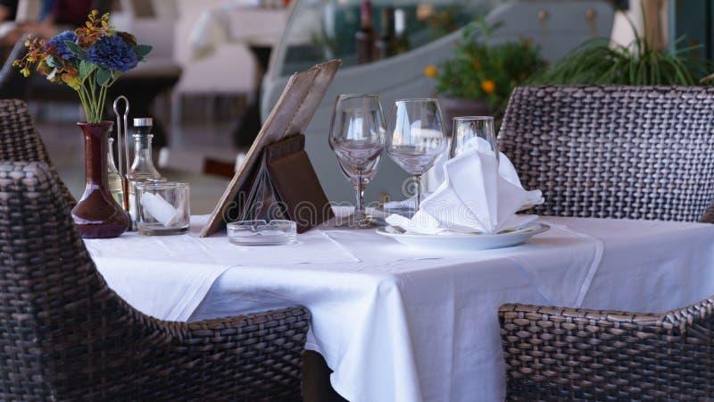 Vit tabell i restaurangen med en st?ende vas av blommor arkivbild