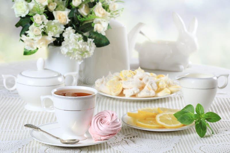 Vit tabell med sötsaker och blommor arkivfoto