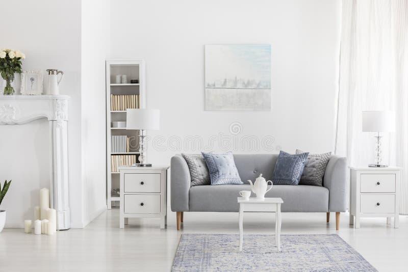 Vit tabell på matta framme av den gråa soffan i lägenhetinre med målning och lampan Verkligt foto arkivfoton