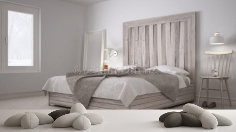 Vit tabell, skrivbord eller hylla med fem mjuka vita kuddar i formen av stjärnor eller blommor, över suddigt sovrum, säng med trä arkivfoton