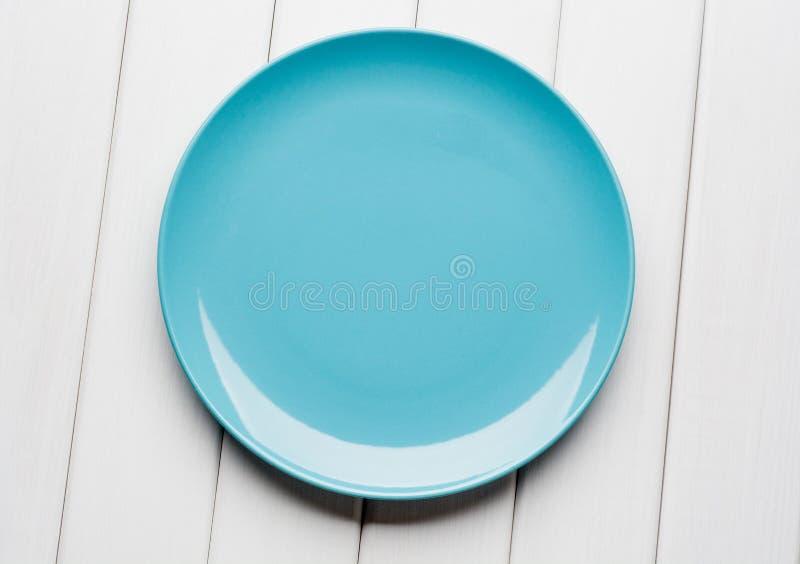 Vit tabellinställning från över Tom blåttplatta på planked trä royaltyfri fotografi