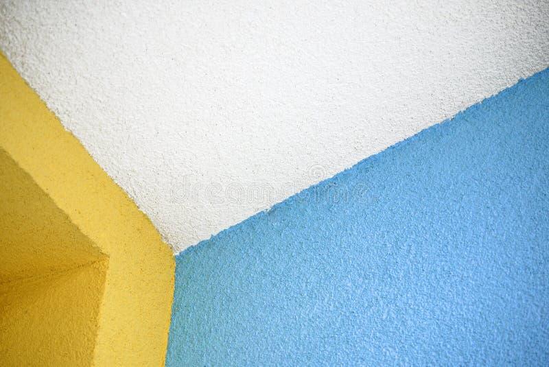 Vit takkant med färgrika blåa och gula väggar som täckas med roughcasten royaltyfri foto