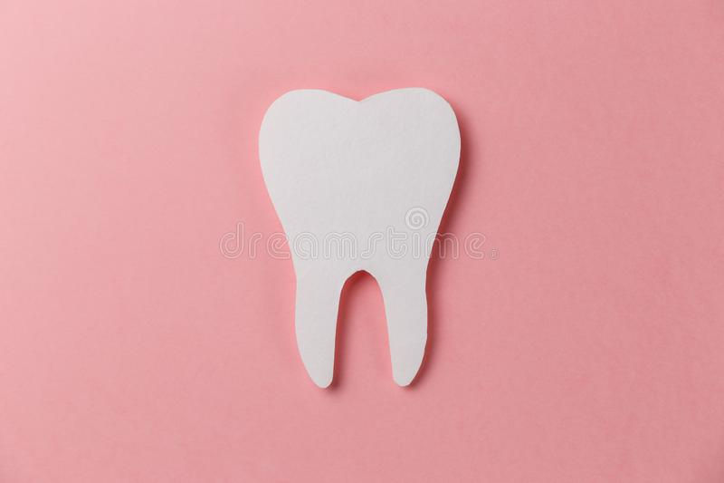 Vit tand på rosa bakgrund royaltyfri foto