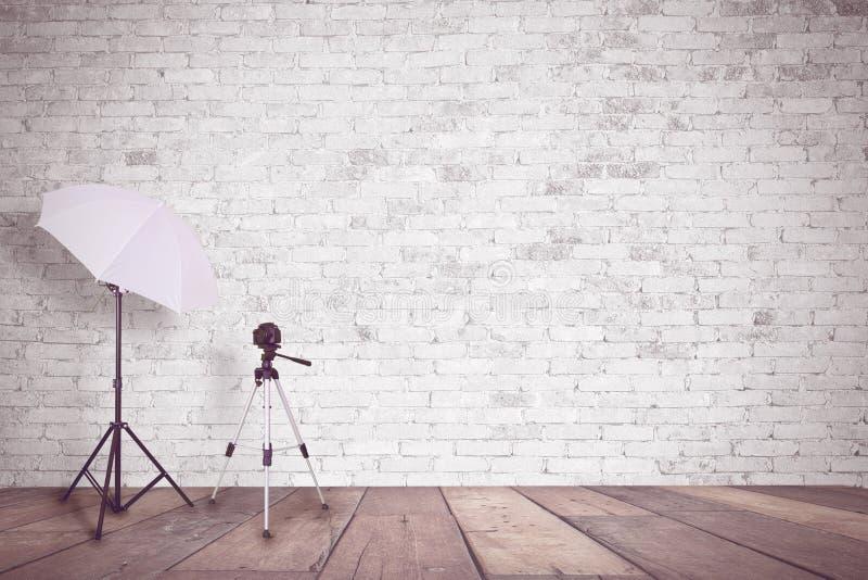 Vit tegelstenvägg i en fotostudio Ett paraply för belysning och en tripod för en kamera tomt kopieringsutrymme arkivfoton