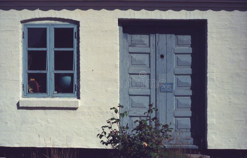 Vit tegelstenvägg med blåa dörrar och ett fönster arkivfoto