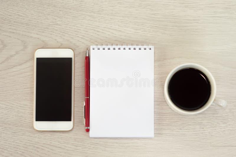 Vit telefon med en kopp kaffe-, notepad- och pennlögn på en vit trätabell arkivfoton