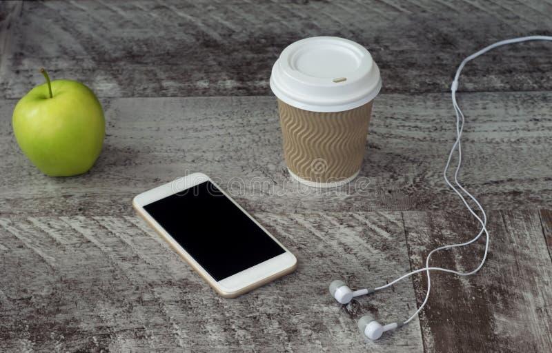 Vit telefon med hörlurar, kaffe och det gröna äpplet på tabellen Arbete hemma frilans royaltyfri fotografi