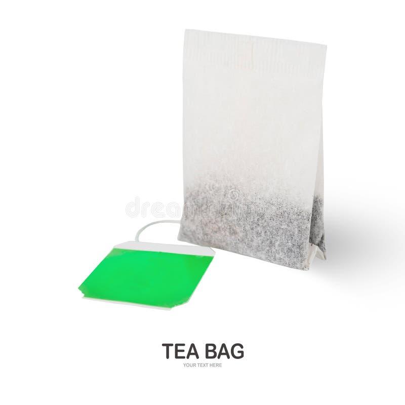 Vit tepåse med den gröna etiketten som isoleras på vit arkivfoton