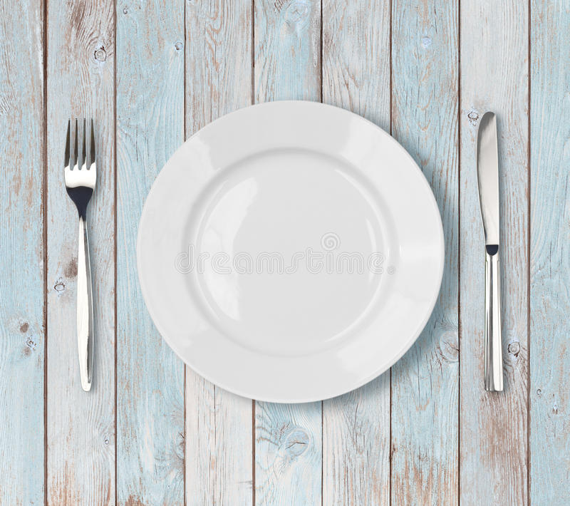Vit tom inställning för matställeplatta på den blåa trätabellen arkivbilder