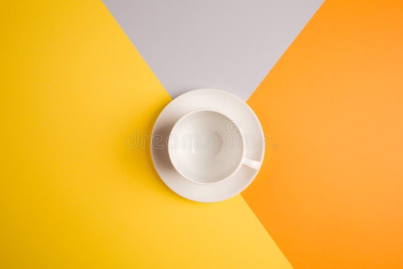 Vit tom kaffekopp på ljus guling-apelsin-beiga-grå färger bakgrund kopieringsspase, lekmanna- lägenhet begrepp av höstkafémenyn arkivbild