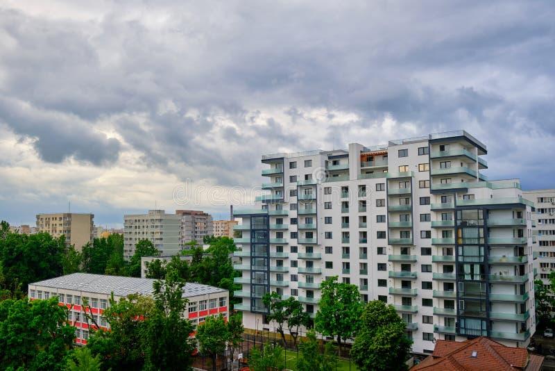 Vit tom lägenhetbyggnad med stormiga moln över Generisk modern arkitektur i Östeuropa Till salu och hyrabegrepp royaltyfria foton