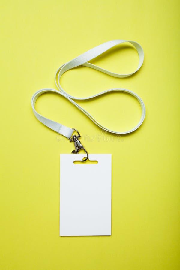 Vit tom legitimationkortetikett med bandet på gul bakgrund, modell royaltyfri foto