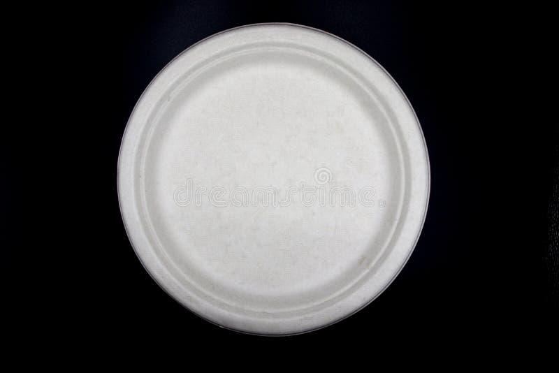 Vit tom pappers- disk, naturlig platta för mat för växtfiber, pappers- platta som isoleras på svart bakgrund arkivbilder