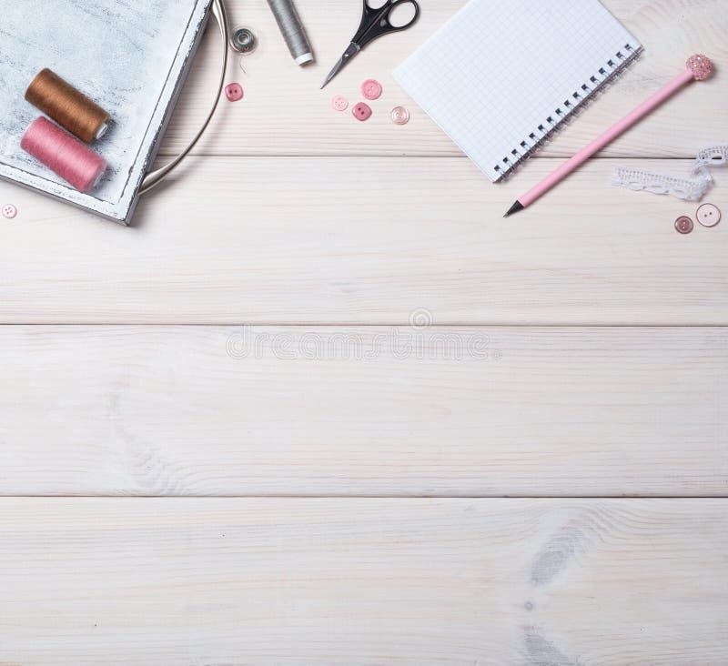 Vit träbakgrund med objekt för att sy Trådar, blixtlås, knappar, sax, anteckningsbok och blyertspenna royaltyfri bild