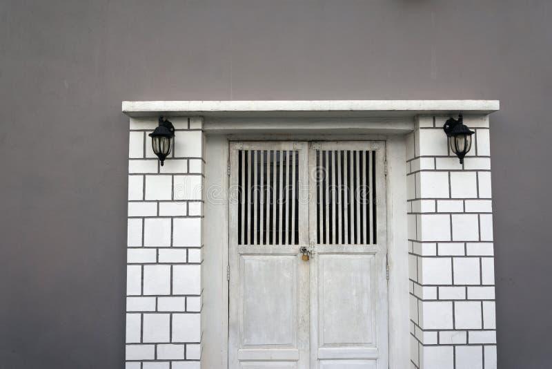 Vit trädörr som låser på väggen i en modern grå färg arkivfoto