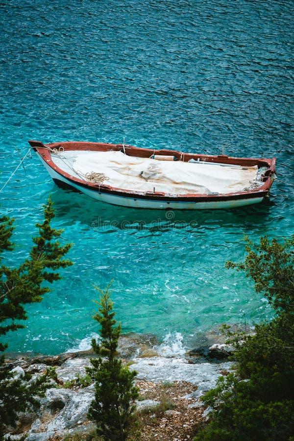 Vit träfiskebåt i fjärd med azurt vatten av medelhavet Vita träd för stenkustcypressar royaltyfria foton