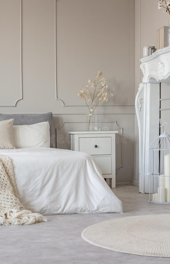 Vit träspisportal i det härliga sovrummet som är inre med vita ark på konungformatsäng royaltyfria foton