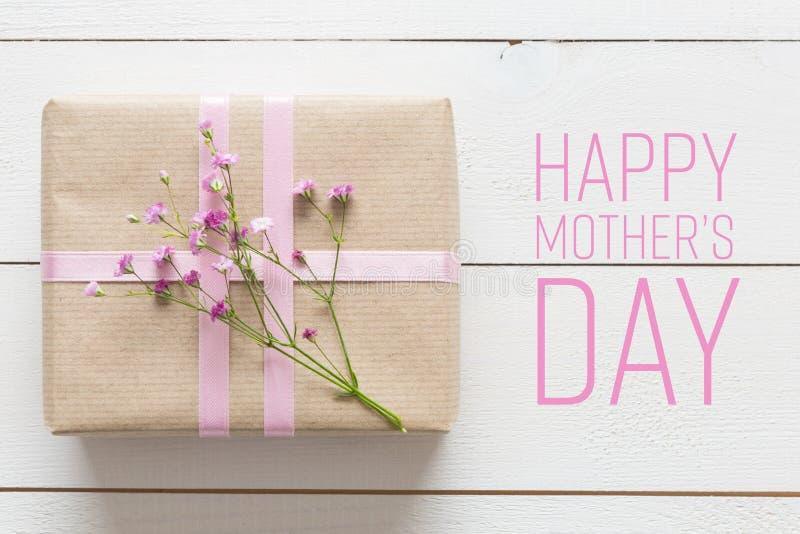 Vit trätabell med rosa färgblommor och en gåva, dag för moder` s royaltyfri bild