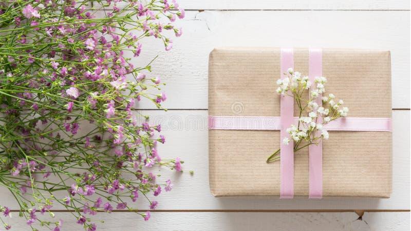 Vit trätabell med rosa färgblommor och en gåva, dag för moder` s arkivfoton