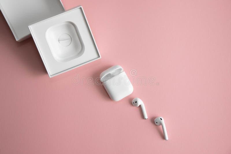 Vit trådlös hörlurar bredvid uppladdaren och en vit öppen ask från dem och att ligga diagonalt på en rosa bakgrund royaltyfri foto