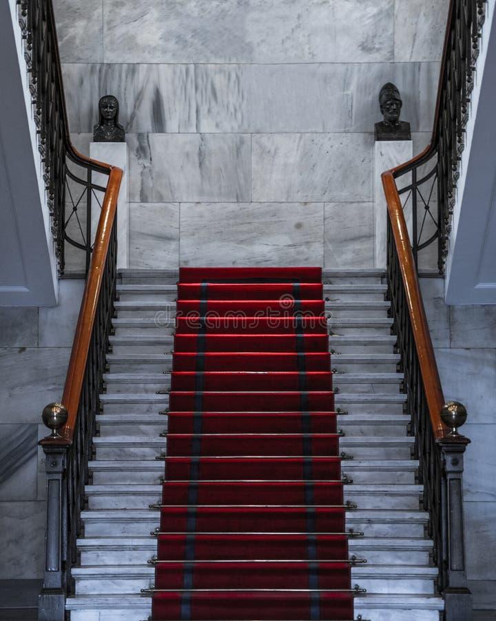 Vit trappuppgång med röd matta överst arkivfoto