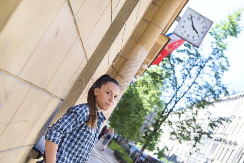 Vit ung flicka med långt hår i en plädskjorta på en stadsstree arkivfoto