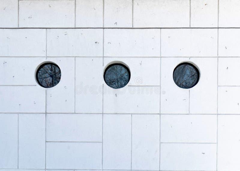 vit vägg i rektanglar och fyrkanter och tre svarta runda fönster stock illustrationer