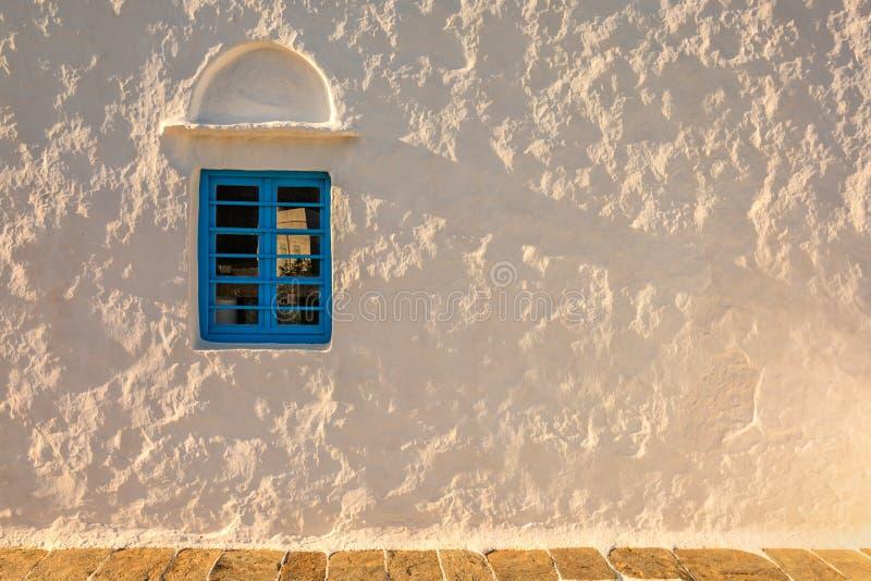 Vit vägg med det blåa fönstret på solnedgången royaltyfria bilder