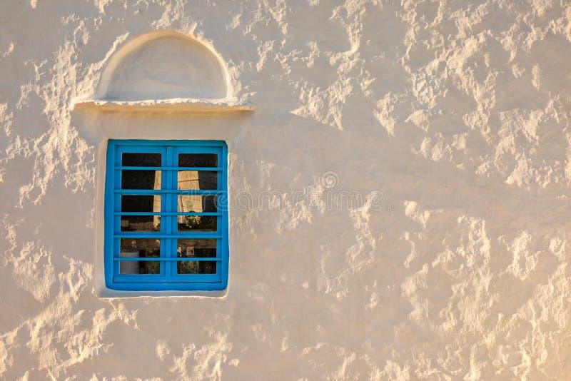 Vit vägg med det blåa fönstret på solnedgången royaltyfria foton