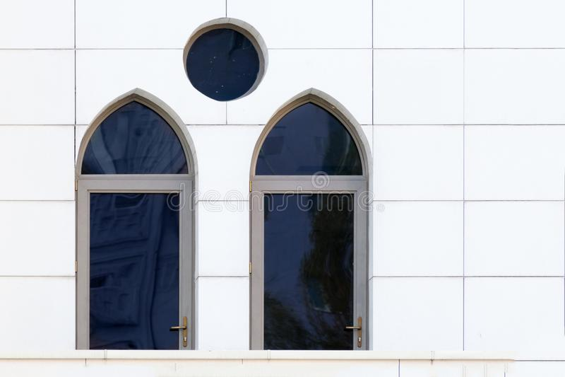 Vit vägg med välvda och runda fönster, detalj av byggnadsyttersida royaltyfri fotografi