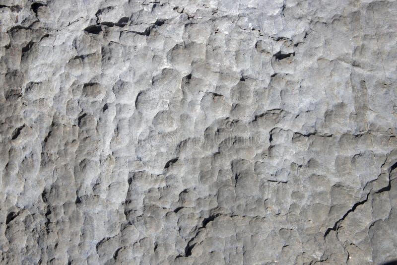 Vit vaggar grov textur Stenyttersidafoto Gå i flisor stena yttersida med skärarefläckar Åldrats stena väggcloseupen arkivfoto