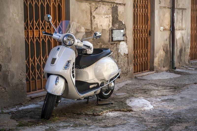 Vit Vespa på en liten ful gata i den gamla staden, Italien arkivfoton